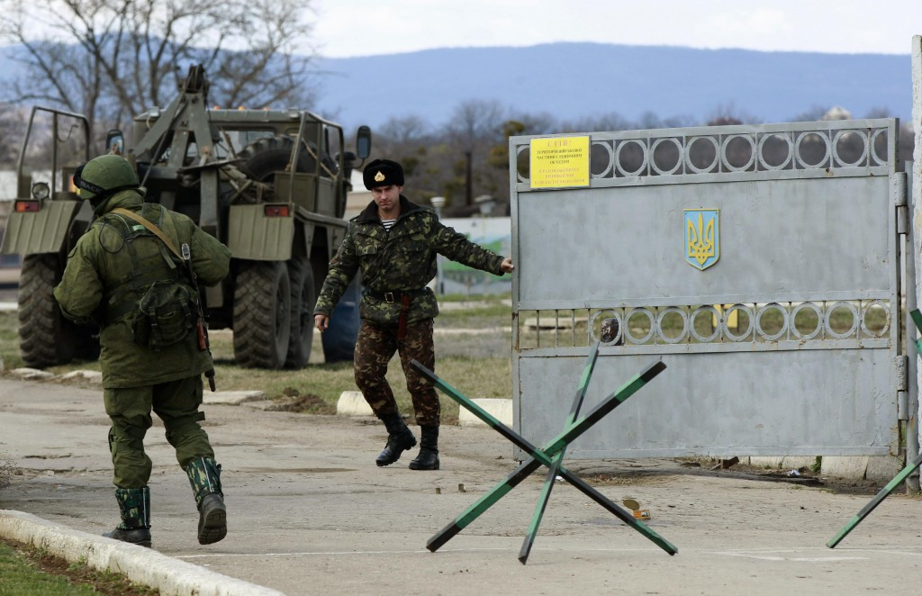 A Ukrainian serviceman closes a gate as an armed man, believed to be Russian serviceman, stands guard outside an Ukrainian military base in Perevalnoye